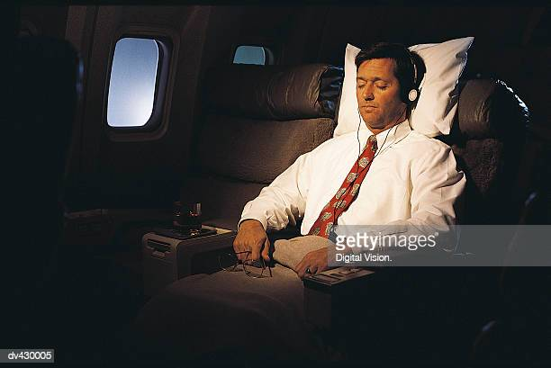 Businessman Sleeping on a Commercial Aeroplane