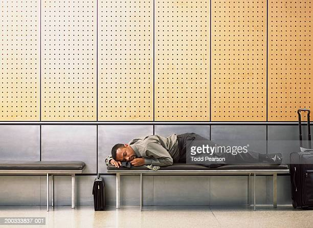 Businessman sleeping on bench in airport