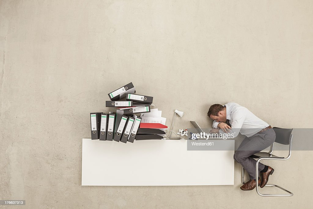 Businessman sleeping on office desk with stack of files : Stock Photo