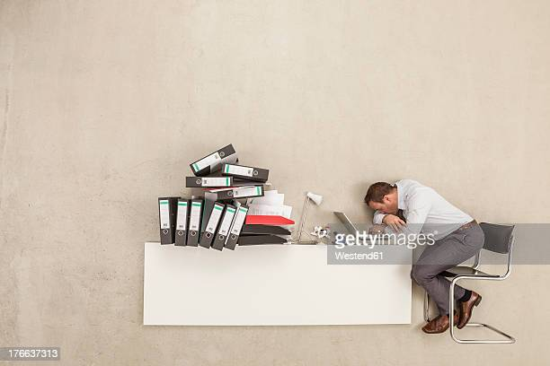 Businessman sleeping on office desk with stack of files