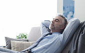 Handsome businessman relaxing at home on the couch, he is sleeping with hands behind head