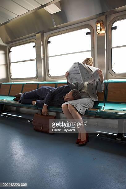 Businessman sleeping on woman's lap