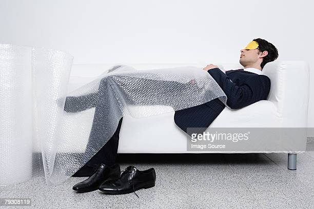 Businessman sleeping under bubble wrap