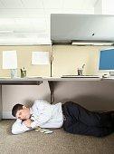 Businessman sleeping under desk