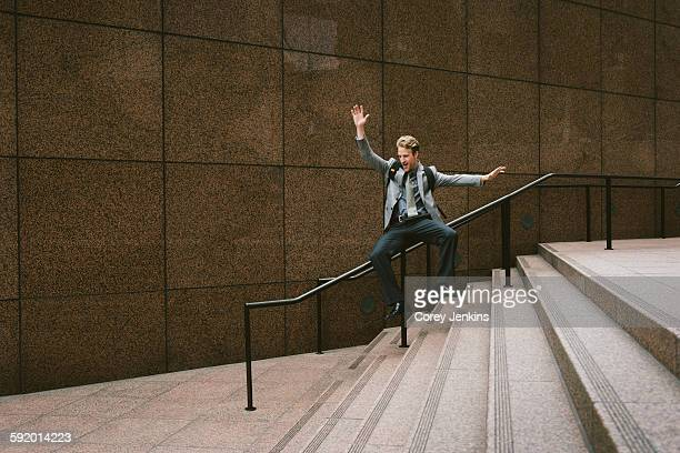 Businessman sliding down city stair handrail