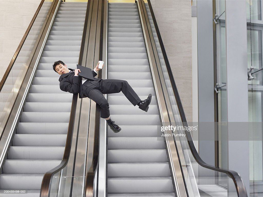 Businessman sliding down handrail of escalator on back holding cup