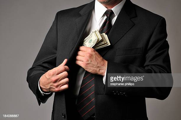 Businessman Slipping a Stack of Cash into His Suit Pocket