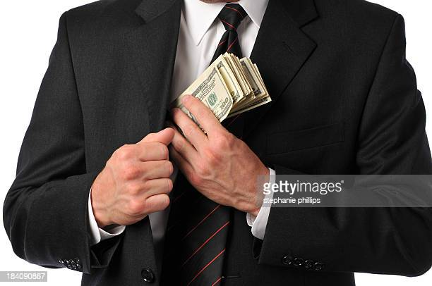 Businessman slipping stack of hundreds in his suit pocket