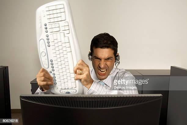 Businessman smashing a keyboard