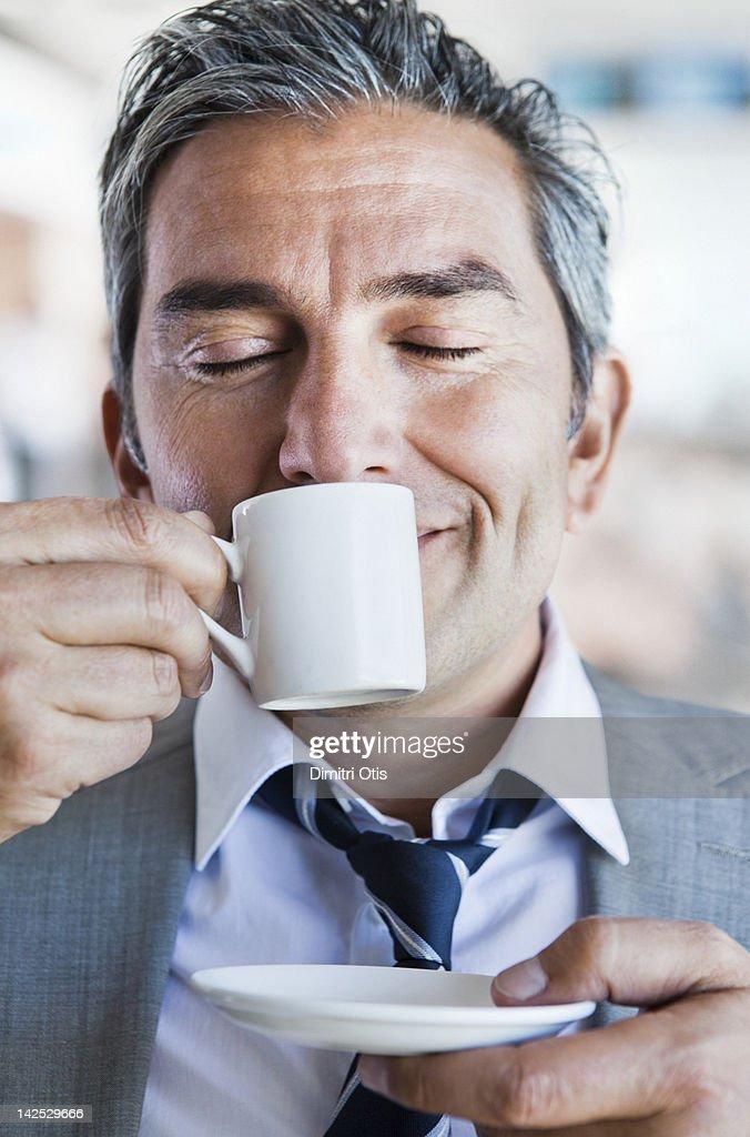 Businessman smelling espresso coffee