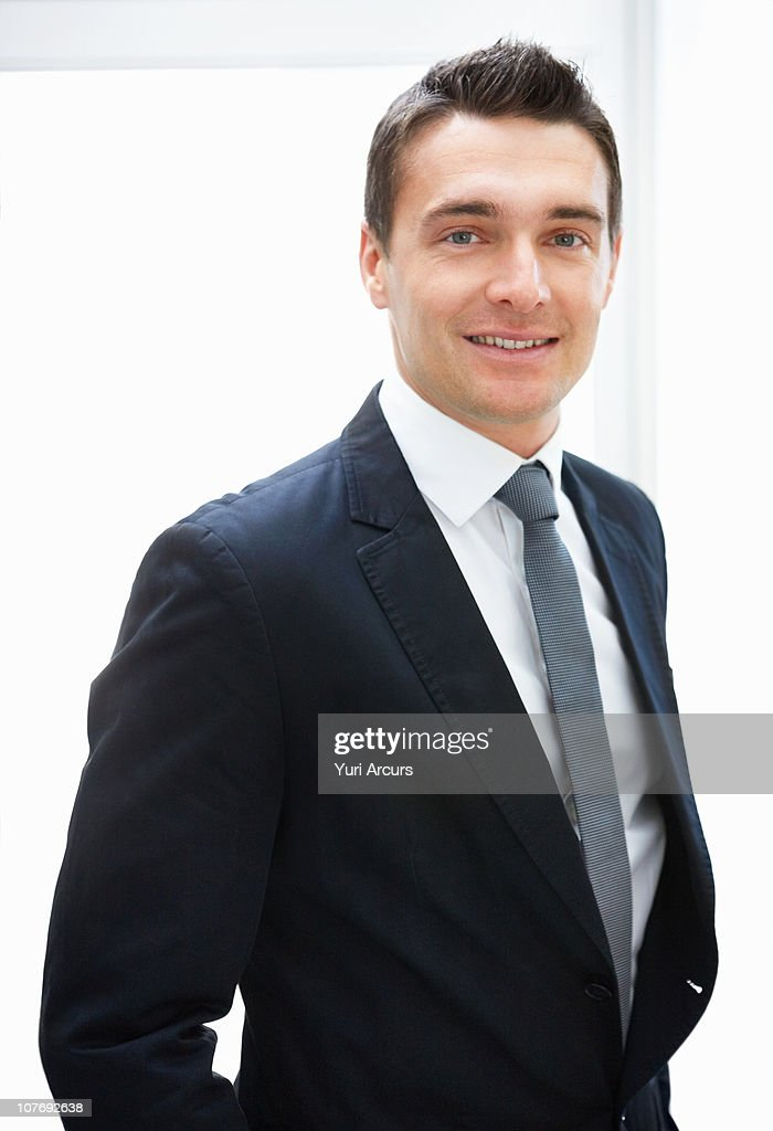 Businessman smiling against white background : Stockfoto