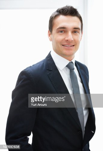 Businessman smiling against white background : Photo