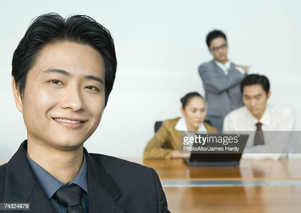 Businessman smiling at camera, team using laptop in background