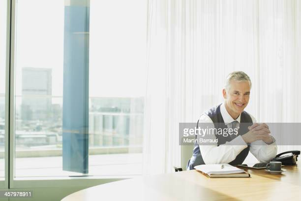 Businessman smiling at desk in office