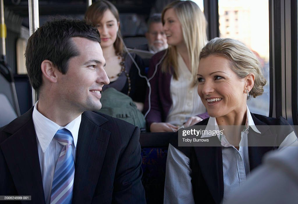 Businessman smiling at woman on bus : Stock Photo