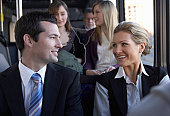 Businessman smiling at woman on bus
