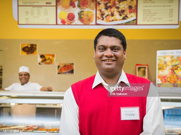 Businessman smiling by restaurant counter