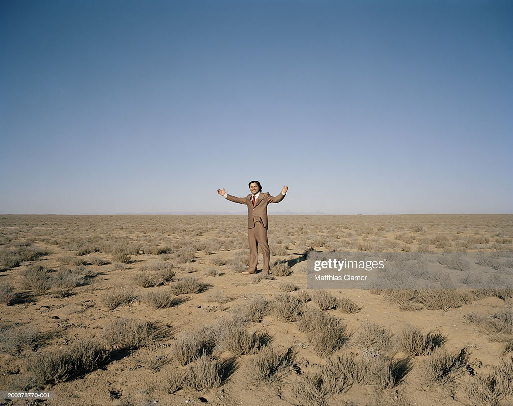 Businessman smiling in desert, portrait : Stock Photo