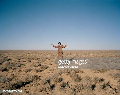 Businessman smiling in desert, portrait : Stock Photo