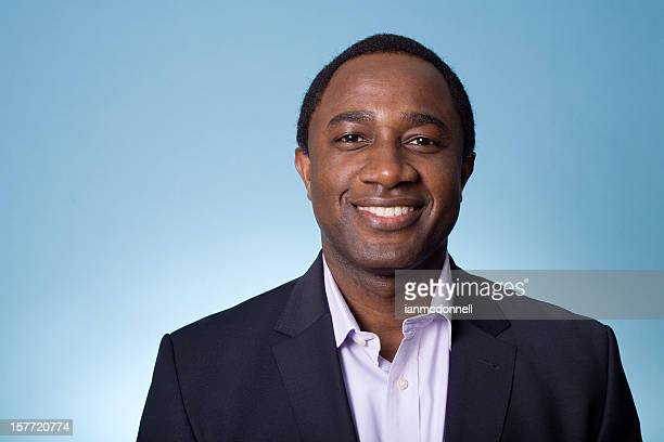 A businessman smiling in front of a blue background