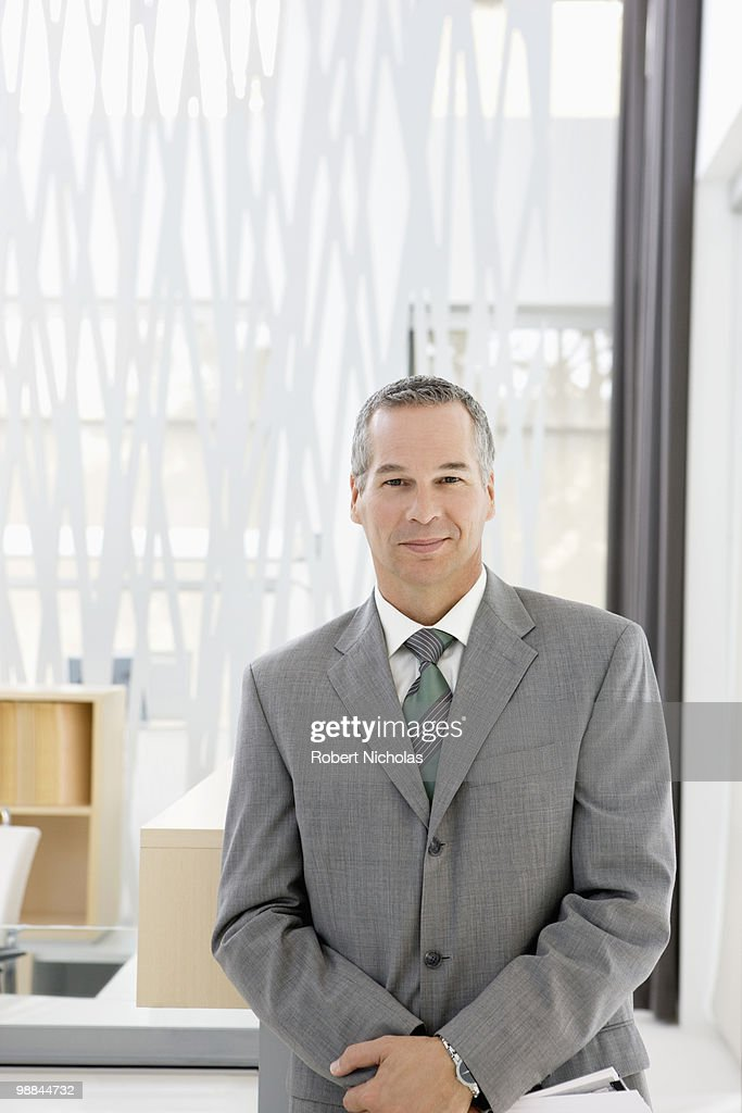Businessman smiling in office : Stock Photo