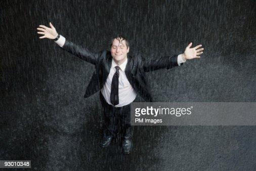 Businessman smiling in rain