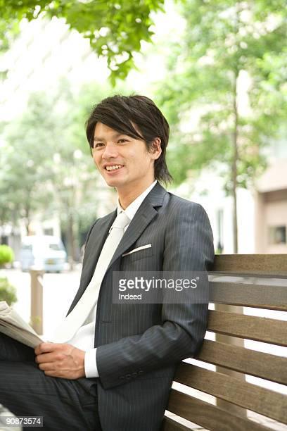 Businessman smiling on bench