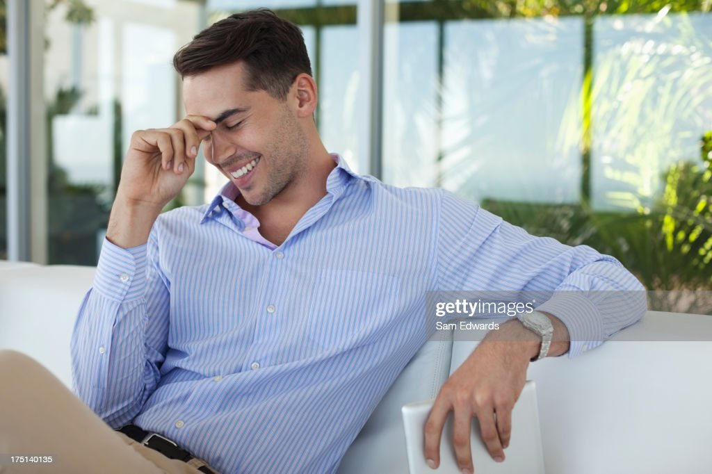 Businessman smiling on sofa : Stock Photo