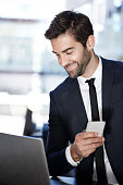 Businessman with laptop and smartphone, smiling