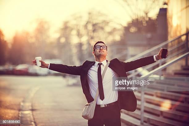 Homme d'affaires souriant avec les bras écartés