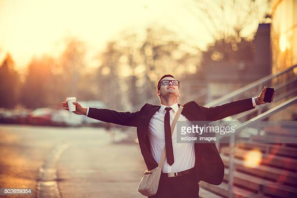 Empresario sonriente con los brazos estirados