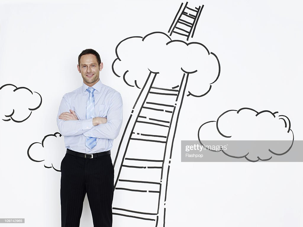 Businessman smiling with ladder in background : Stock Photo