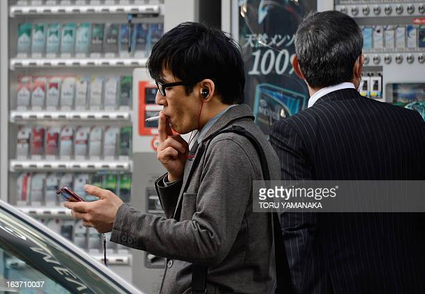A businessman smokes a cigarette in Tokyo on March 13 2013 Japan Tobacco said that Tokyo's partial sale of its stake in the former monopoly would...
