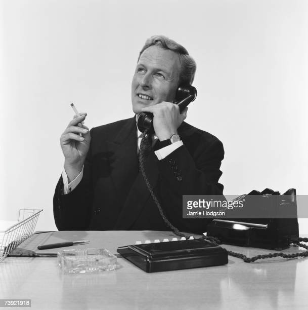 A businessman smokes a Guards cigarette during a phonecall 13th August 1959