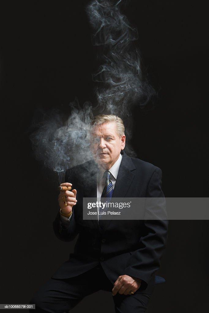 Businessman smoking cigar, portrait : Stock Photo