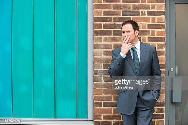 Businessman Smoking Cigarette Outdoors