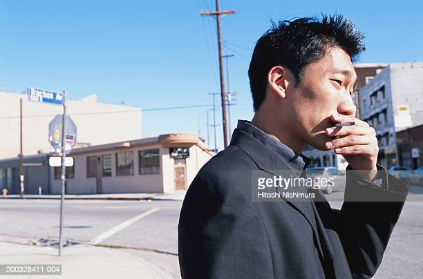 Businessman smoking, side view