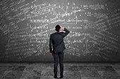 Rear view of pensive businessman scratching his head and looking at mathematical equation on wall