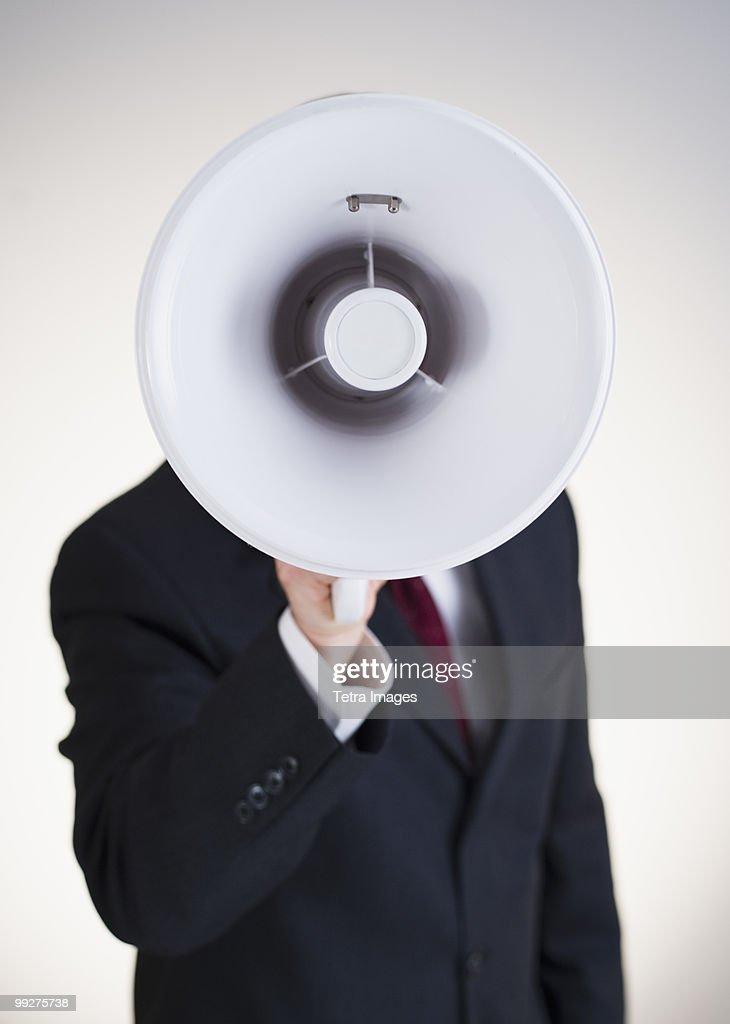 Businessman speaking into bullhorn