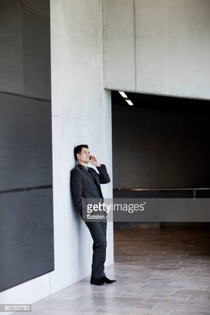 Businessman speaking on mobile phone,leaning again
