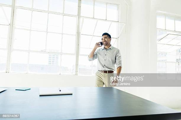 Businessman speaking on smartphone by office window