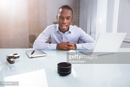 Businessman Speaking On Wireless Speaker : Stock Photo