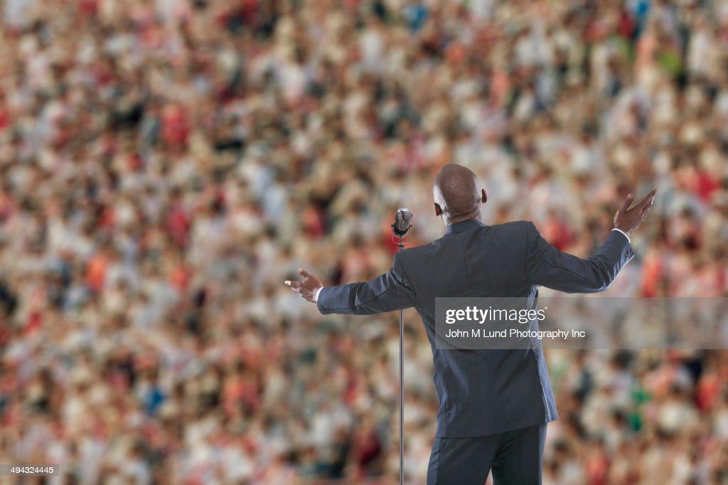 Businessman speaking to crowd : Stock Photo