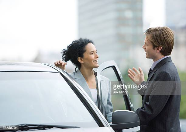 Businessman speaking to woman as she gets into car