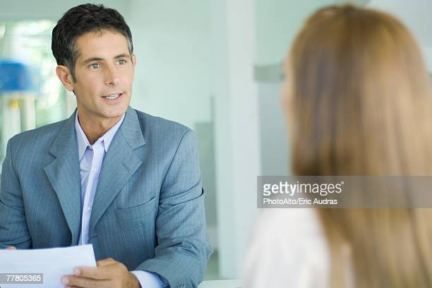 Businessman speaking to young woman