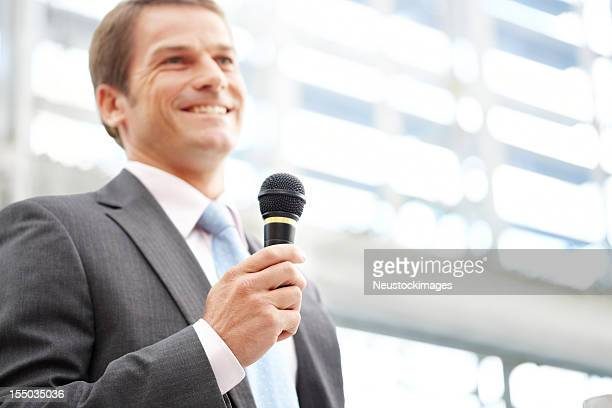 Businessman Speaking With a Microphone