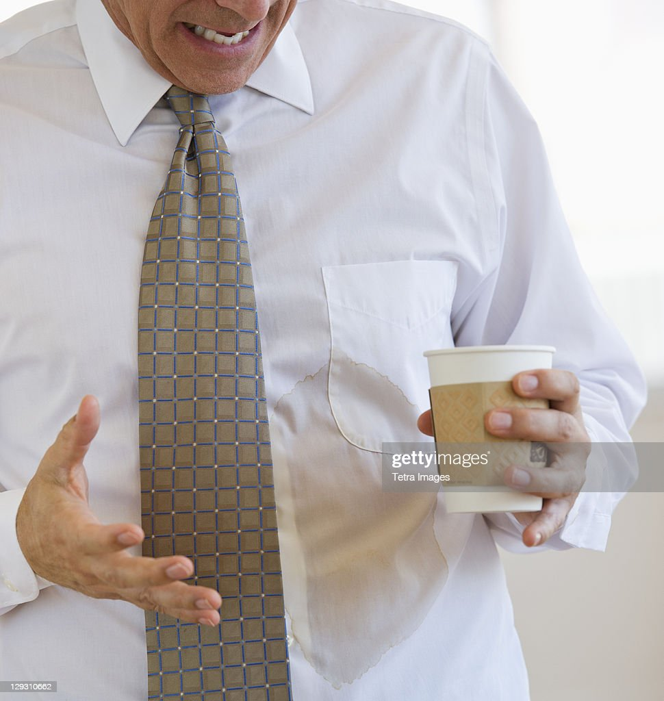 Businessman spilling coffee on shirt