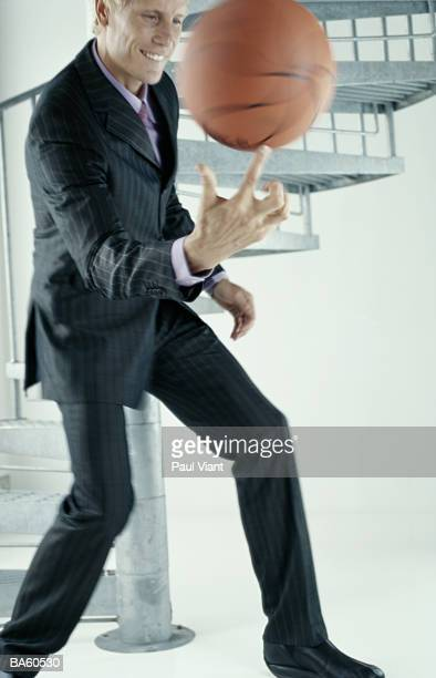 Businessman spinning baseball on fingertip