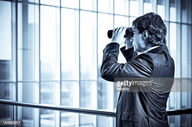 Businessman spying with binoculars