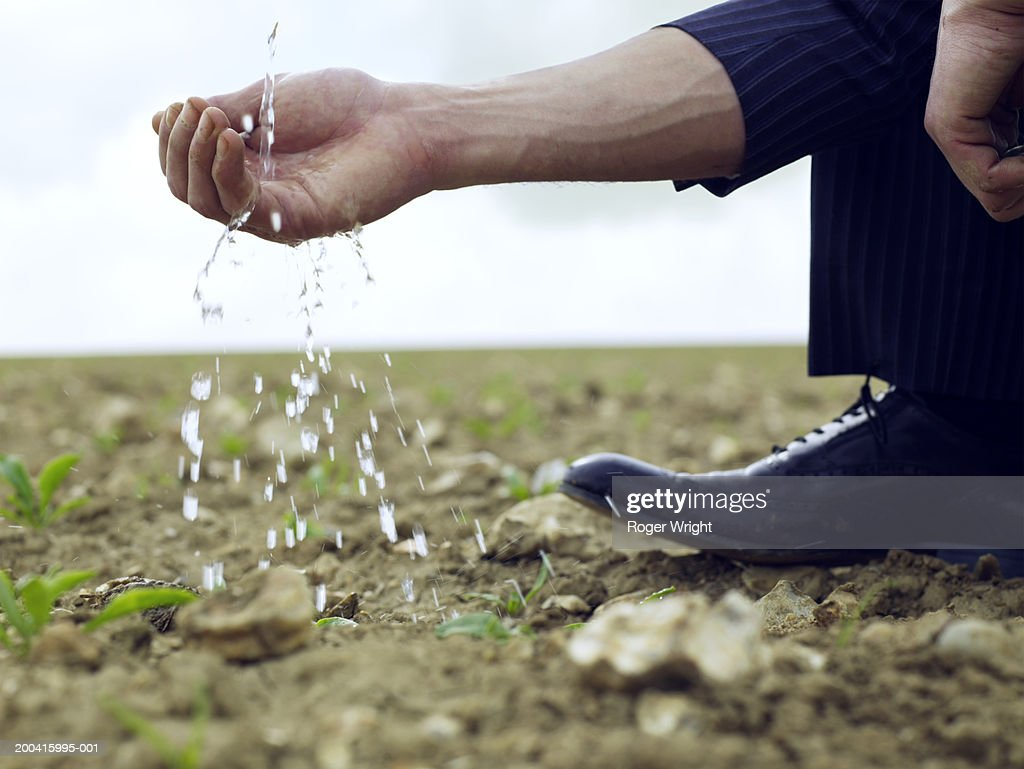 Businessman squatting in field, splashes of water by hand, close-up